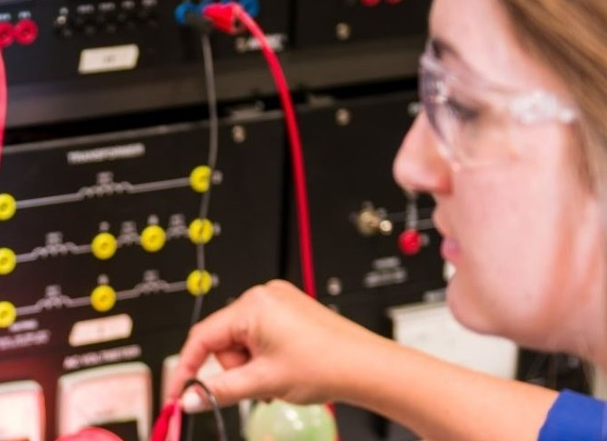 Lady in safety glasses using electronic equipment
